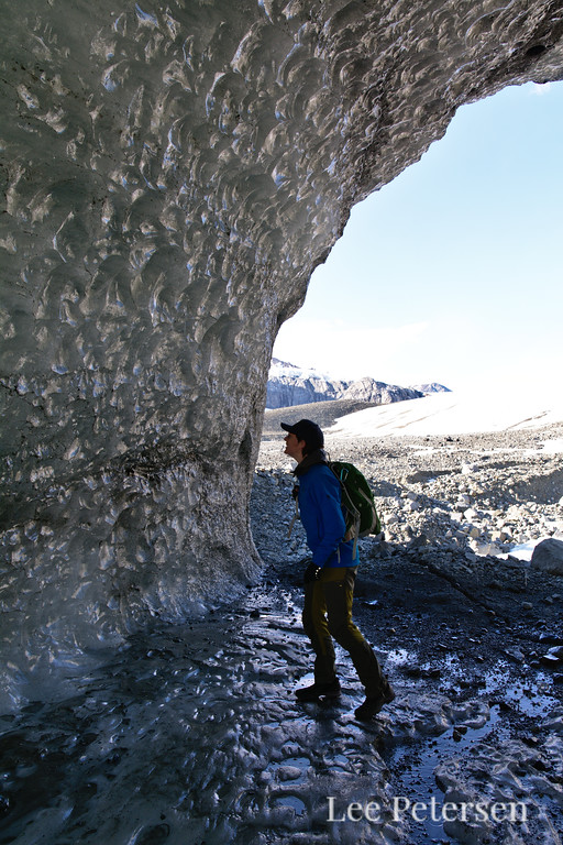 A person inspecting the walls of a glacial ice tunnel